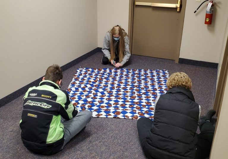 Lakota Neuman and Tim Giacobbe, TRIO Upward Bound students, and Michele Lauck, Upward Bound Study Labe Instructor, making fleece blankets for children helped by the Department of Human Services.